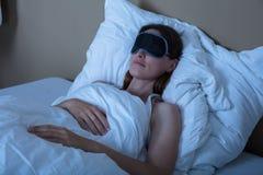 睡觉在与眼罩的床上的妇女 库存图片