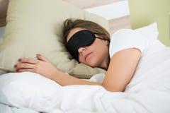 睡觉在与眼罩的床上的妇女 免版税库存图片