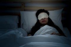 睡觉在与眼罩的床上的美丽的妇女 免版税库存照片
