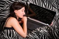 睡觉在与笔记本个人计算机的床上的妇女 免版税图库摄影