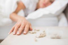 睡觉在与药片的床上的妇女在前景 免版税库存照片