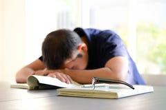 睡觉在与被打开的书的桌上的年轻人 免版税图库摄影