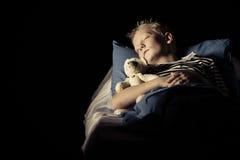 睡觉在与长毛绒玩具熊的床上的逗人喜爱的男孩 免版税库存图片