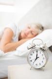 睡觉在与闹钟的床上的妇女在前景在卧室 免版税库存图片