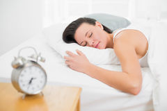 睡觉在与闹钟的床上的妇女在床头柜上 免版税库存照片