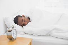 睡觉在与闹钟的床上的蓬松卷发人在前景 免版税库存照片