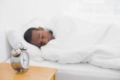 睡觉在与闹钟的床上的蓬松卷发人在前景 免版税库存图片