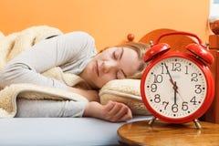 睡觉在与集合闹钟的床上的妇女 免版税库存图片