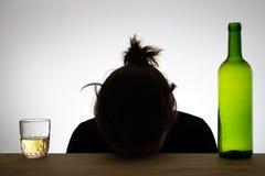 睡觉在书桌上的一名醉酒的妇女的剪影 免版税库存图片