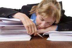 睡觉在书桌上的被用尽的女实业家 免版税库存图片
