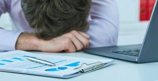 睡觉在书桌的一台膝上型计算机的年轻疲乏的劳累过度的商人在工作在他的办公室 最后期限概念 免版税库存图片