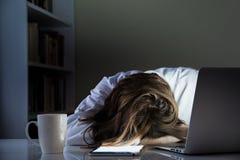 睡觉在书桌的疲乏的人在有起动的计算机和片剂个人计算机的家庭办公室 免版税图库摄影