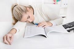 睡觉在书桌的白肤金发的劳累过度的女实业家或实习生 库存照片
