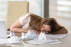 睡觉在书桌的被用尽的疲乏的妇女在劳累过度以后在办公室 免版税库存照片