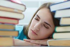 睡觉在书的一个疲乏的学生女孩的画象 图库摄影