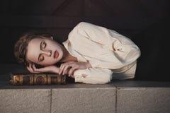 睡觉在书的一个美丽的梦想的女孩的减速火箭的画象户外 软葡萄酒定调子 免版税图库摄影