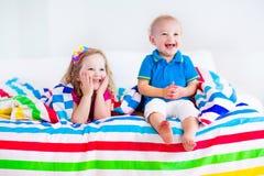 睡觉在五颜六色的毯子下的愉快的孩子 免版税库存图片