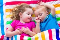 睡觉在五颜六色的毯子下的滑稽的孩子 库存照片