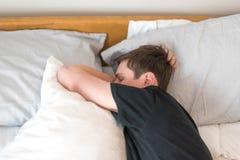 睡觉在他的在早晨光的边的年轻人 免版税库存照片