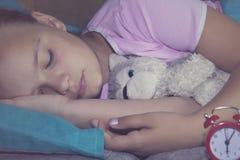 睡觉在他的床上的小白肤金发的孩子与玩具和在红色闹钟附近 图库摄影