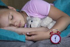 睡觉在他的床上的小白肤金发的孩子与玩具和在红色附近 库存图片