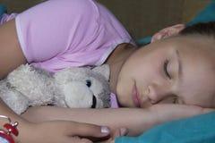 睡觉在他的床上的小白肤金发的孩子与玩具和在红色附近 免版税库存照片