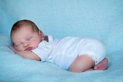 睡觉在他的肚子全长旁边外形蓝色背景的新出生的婴孩 图库摄影