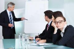 睡觉在会议的乏味女实业家 免版税库存图片
