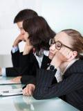 睡觉在会议的乏味女实业家 免版税库存照片