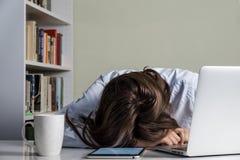睡觉在便携式计算机和片剂个人计算机前面的书桌的疲乏的女孩 免版税库存图片