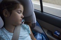 睡觉在儿童安全位子的儿童女孩在旅行期间 免版税库存图片