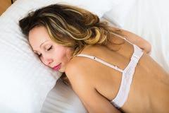 睡觉在内衣的秀丽妇女 免版税图库摄影