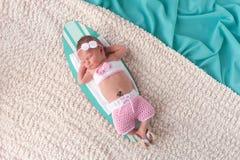 睡觉在冲浪板的新出生的女婴 免版税库存照片