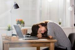 睡觉在办公桌上的年轻女实业家 免版税库存图片