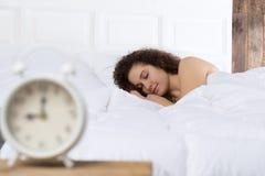 睡觉在单独床上的美丽的女孩 免版税库存图片