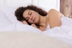 睡觉在单独床上的美丽的女孩 库存图片