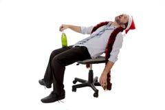 睡觉在喝的醉酒的商人香槟以后在办公室圣诞晚会 库存照片