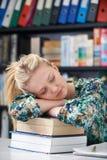 睡觉在图书馆里的疲乏的女性少年学生 库存照片