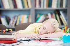 睡觉在图书馆里的疲乏的学生 免版税库存照片