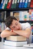睡觉在图书馆里的疲乏的男性少年学生 库存图片