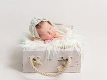 睡觉在土气箱子,佩带的帽子的孩子 库存图片