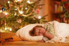 睡觉在圣诞树下的小逗人喜爱的白肤金发的男孩 图库摄影