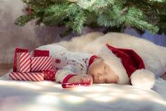睡觉在圣诞树下的逗人喜爱的新出生的婴孩在戴圣诞老人帽子的红色礼物附近 库存照片