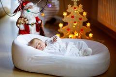 睡觉在圣诞树附近的一个星期的新出生的女婴 免版税图库摄影