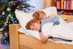睡觉在圣诞节的床上的两个小白肤金发的兄弟姐妹男孩 库存照片