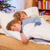 睡觉在圣诞节的床上的两个小白肤金发的兄弟姐妹男孩 库存图片
