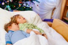 睡觉在圣诞节的床上的两个小白肤金发的兄弟姐妹男孩 免版税库存照片