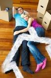 睡觉在地板上的逗人喜爱的夫妇的综合图象 库存照片