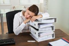 睡觉在堆的女实业家文件夹 免版税库存照片