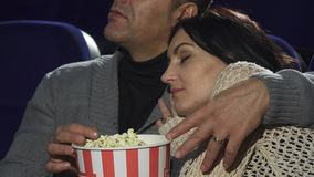睡觉在她的丈夫肩膀的成熟妇女在戏院 免版税库存图片
